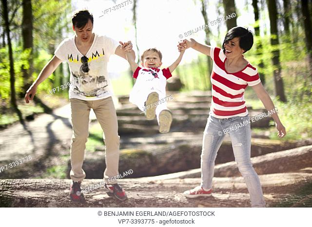 parents swinging toddler child on hands in forest, at Herrenchiemsee, Chiemsee, Bavaria, Germany