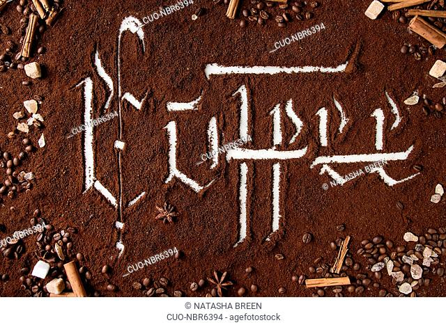 Calligraphic inscription gothic letters coffee over ground black coffee scattered on white marble with roasted beans, sugar and cinnamon