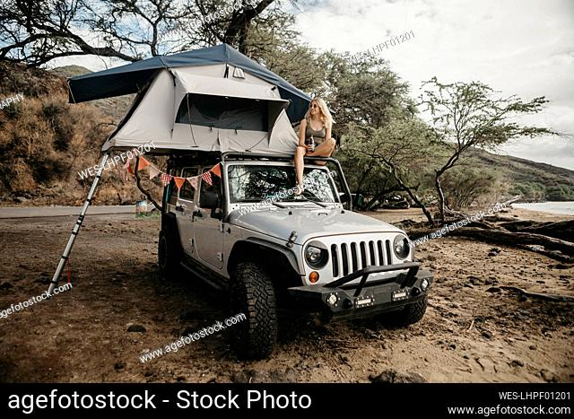 Young woman enjoying drink while sitting on tent over jeep at Maui, USA, Hawaii