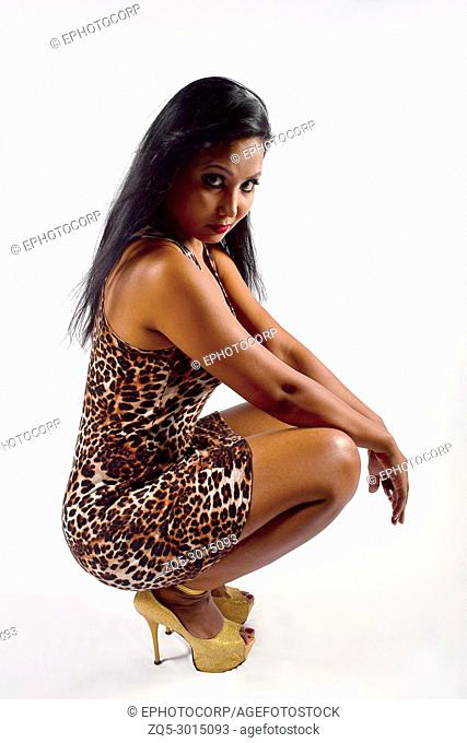 Model wearing leopard short dress sitting on haunches. Indoor Shoot. Grey Background, Pune, Maharashtra