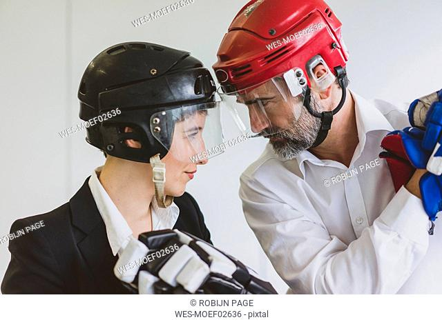 Businesswoman and businessman wearing ice hockey equipment in office