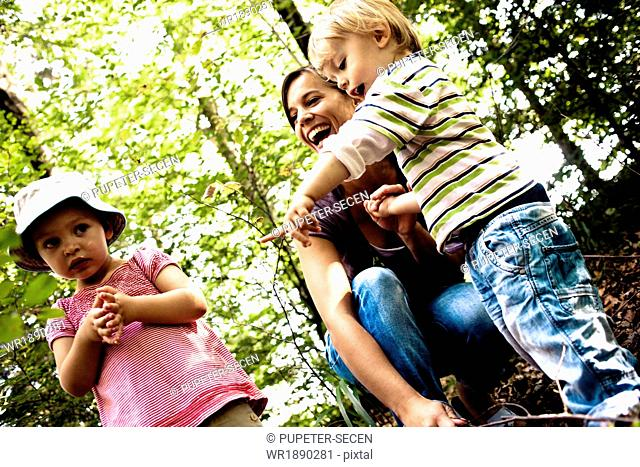 Mother and children in forest, having fun, Bavaria, Germany