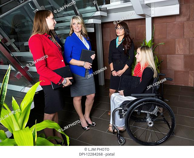 Four professional business women in the lobby of an office, one of which is a paraplegic in a wheelchair; St. Albert, Alberta, Canada