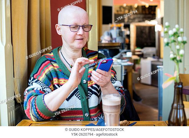 Tilburg, Netherlands. Middle aged balding woman communicating with her smartphone while sitting in a cafe, drinking coffee