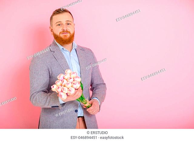 Handsome bearded man holding bouquet of tulips in hand on pink background. 8 march. copy space