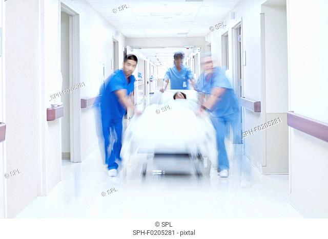 Medical team pushing patient on bed