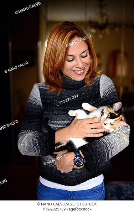 Interior portrait of attractive young woman hugging a calico cat