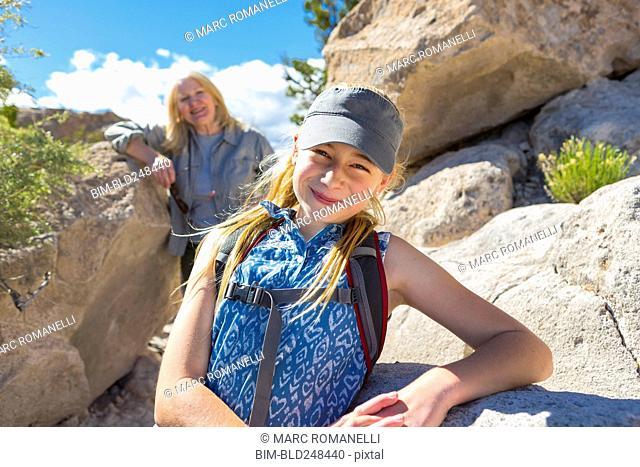 Portrait of Caucasian girl and grandmother hiking near rocks