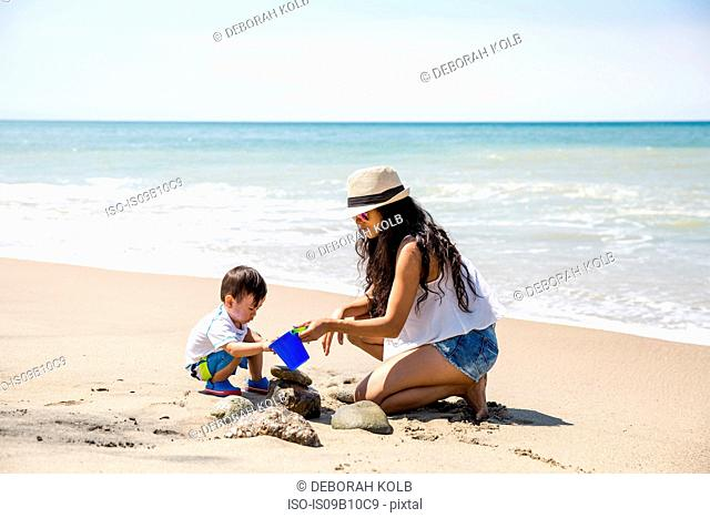 Mother and baby son playing with bucket on beach, Malibu, California, USA