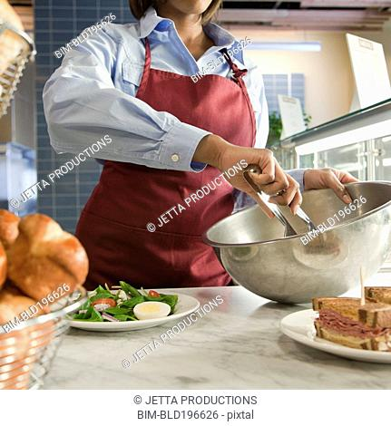 African American worker mixing salad in cafe