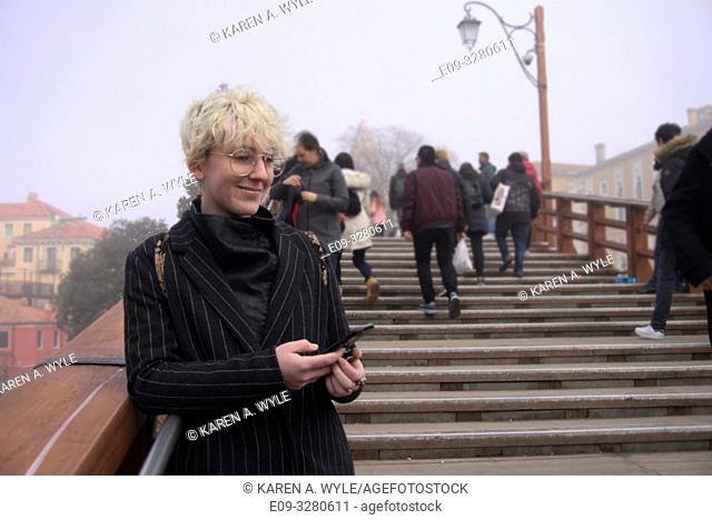 Stylish young woman in pin-stripe coat, wire-rim glasses, blond-white short hair, on Accademia bridge with little smile holding phone, foggy day, Venice, Italy