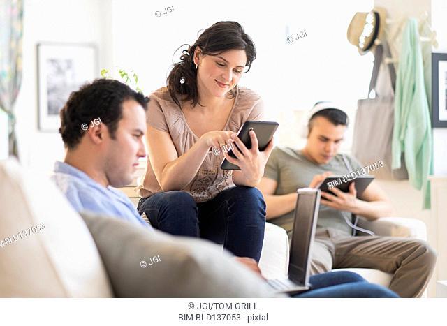 Hispanic friends using technology in living room
