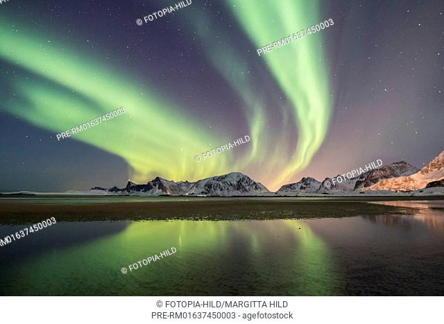 Aurora borealis north of Yttersand, Moskenesøya, Lofoten, Nordland, Norway, March 2017, looking northeast over the Vareidsundet to Vareid with the mountains...