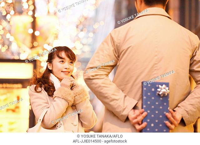 Young Japanese woman receiving present from boyfriend downtown Tokyo