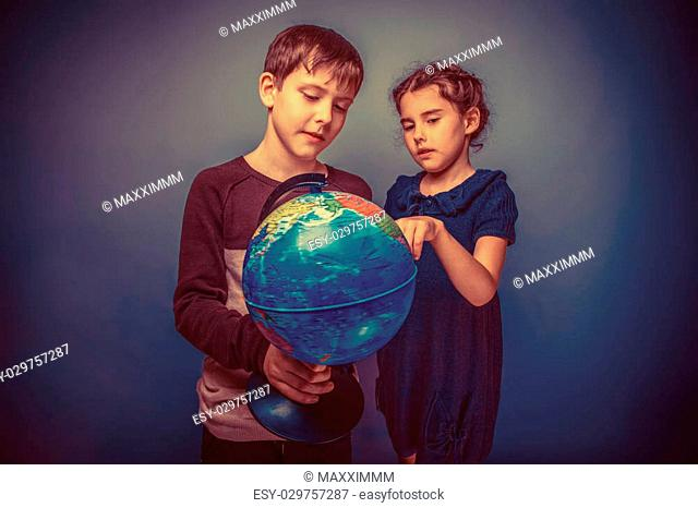 Teen boy and girl of European appearance seven years are holding a globe view it on a gray background, travel, globe retro