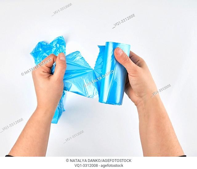 female hands tear off a transparent blue bag for a bin from a roll, white background, top view