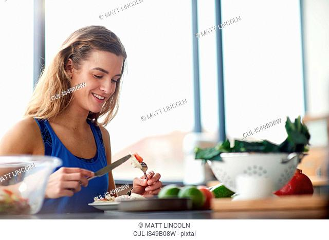 Young woman at kitchen table eating feta salad
