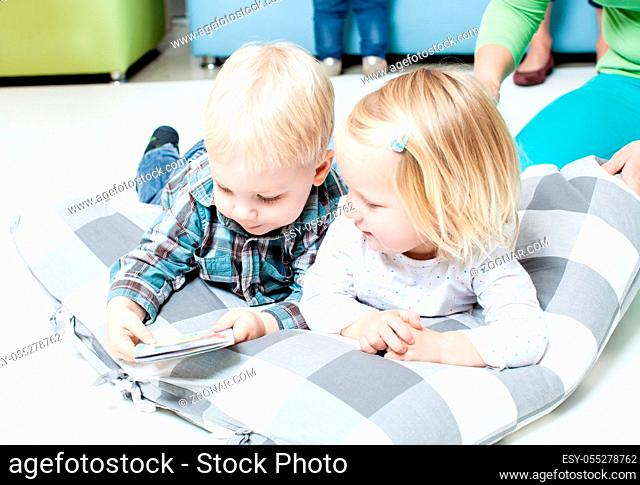 Little boy and girl enthusiastically reading a book lying on the floor