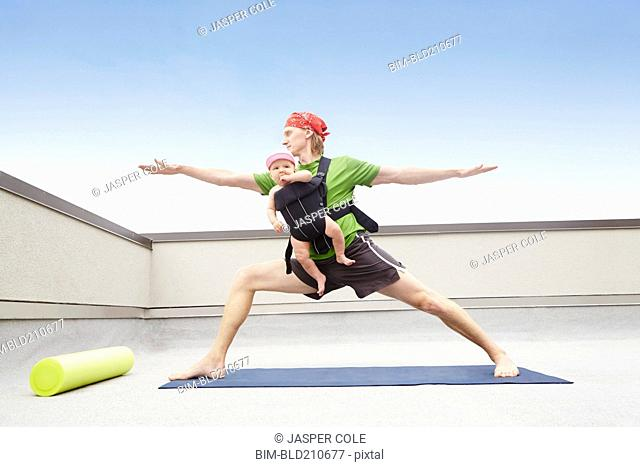Father practicing yoga and holding baby