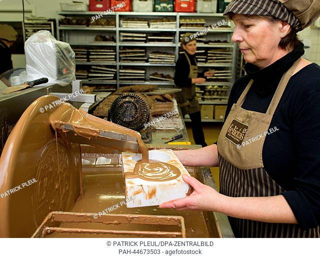 An employee of the Confiserie Felicitas GmbH makes chocolates in Hornow, Germany, 02 December 2013. On the same day the first stone was layed for an extened...