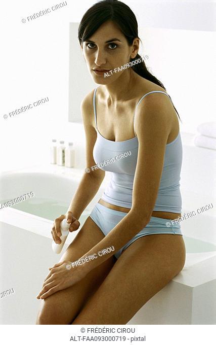Woman sitting on edge of bathtub, putting moisturizer on leg, looking at camera