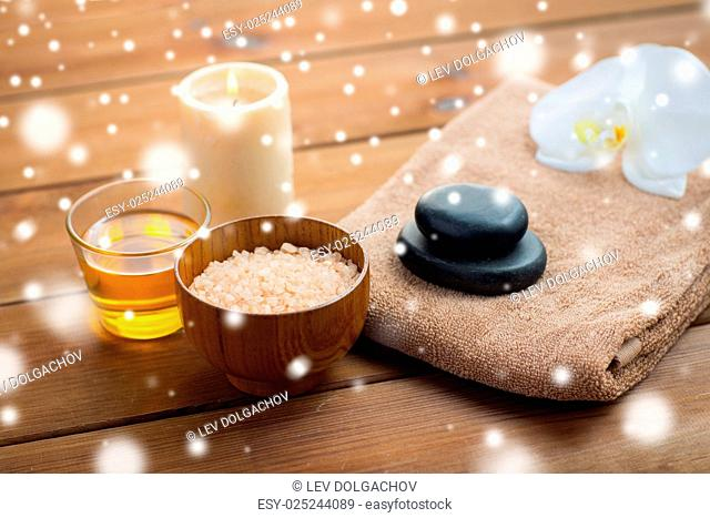 beauty, spa, bodycare, natural cosmetics and concept - himalayan pink salt with honey in glass and bath towel on wooden table over snow