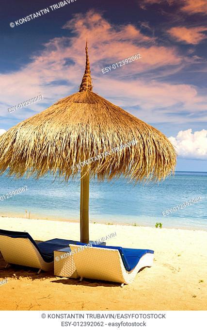 Sea Coastline with Grass Sun Umbrella and Beach Beds