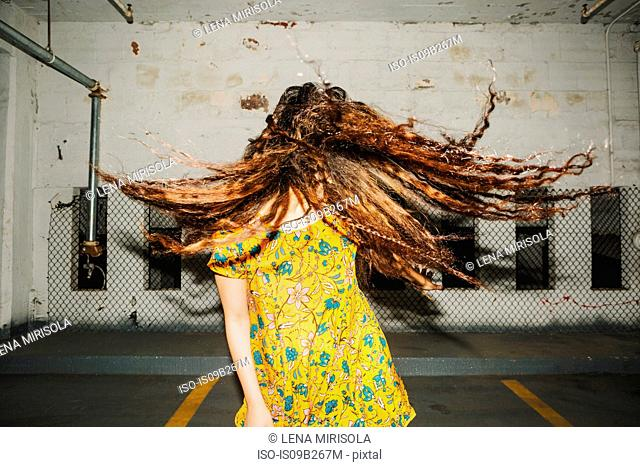 Front view of young woman shaking her long wavy hair in indoor carpark
