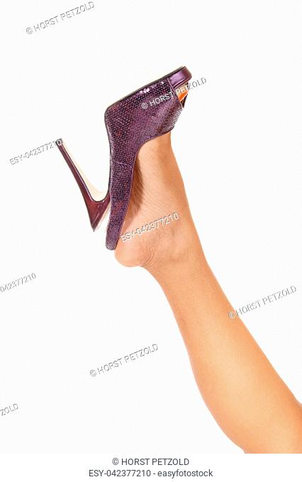 A close up image of a leg with a purple high heel lifted up isolated .over white background