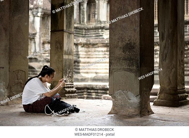 Cambodia, Siem Reap, Angkor Wat, tourist taking pictures of temple with smartphone
