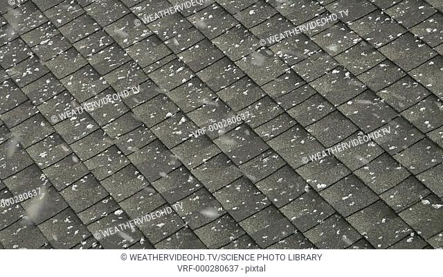 Snowflakes settling on a tiled roof. Filmed in the USA in early spring