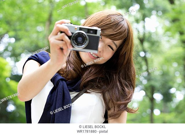 A woman in a Kyoto park holding a camera and laughing