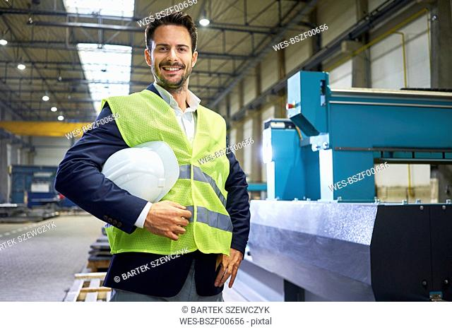 Portrait of smiling manager holding hard hat in factory