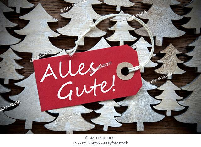 Red Christmas Label With Ribbon On Wooden Christmas Trees Background. Vintage Or Rustic Style. Label With German Text Alles Gute Means Best Wishes For Christmas...