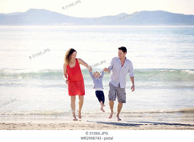 Woman wearing red dress and man wearing shorts standing on a sandy beach by the ocean, swinging young boy by hands