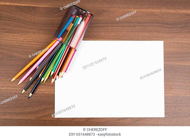 Blank paper with crayons on wooden table