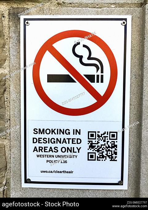 A smoking regulation, complete with words, pictograph, and a QR code on the wall of a college campus, Ontario, Canada. The sign is mainly of historical interest...