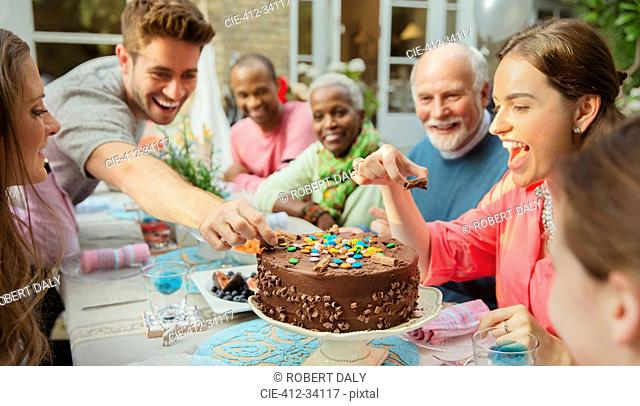 Family reaching for candy on chocolate birthday cake at patio table