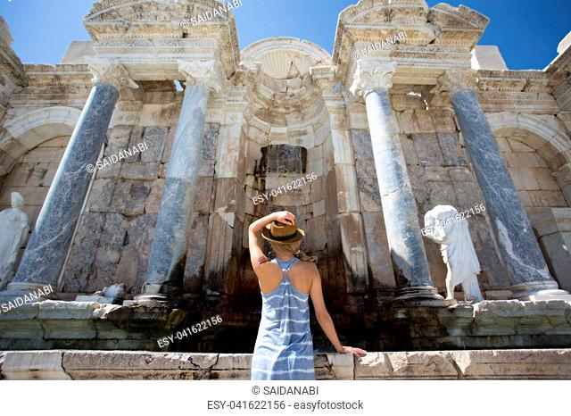 backview portrait of woman traveller wearing long dress and hat in ancient city of Sagalasoss