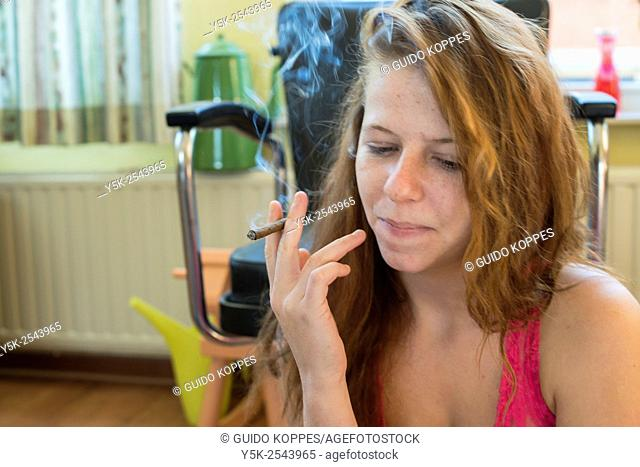 Tilburg, Netherlands. Young woman wearing just a shirt smoking a cigarillo, while sitting down in a living room