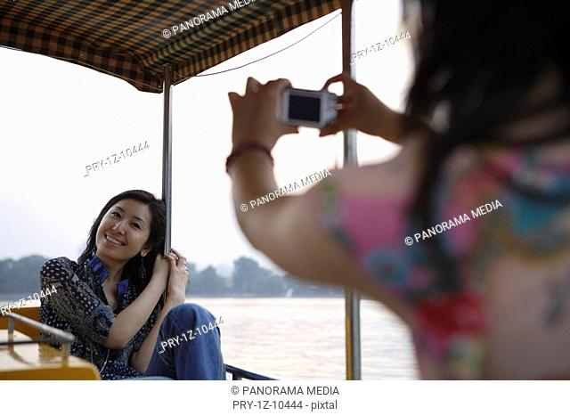Young woman photographing friend