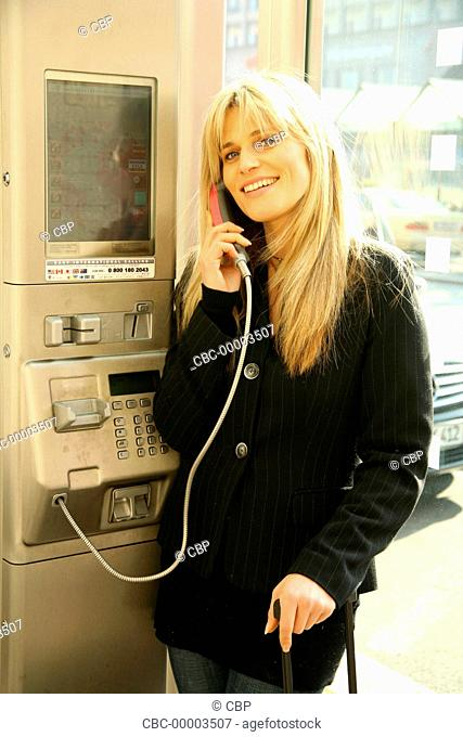 Young Woman Using a Payphone