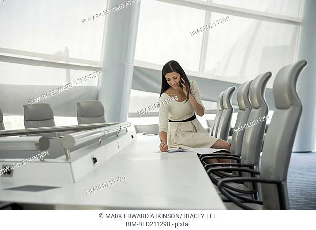 Mixed race businesswoman on cell phone in conference room