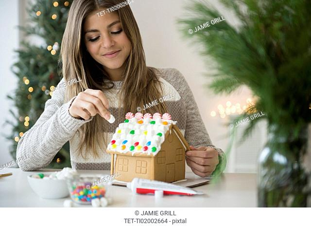 Young woman preparing gingerbread house