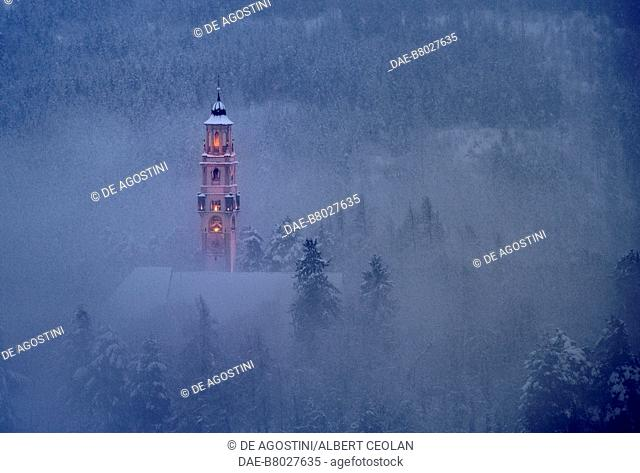 The lighted bell tower of the church of the Assumption of Mary, amidst snow and fog, Cavalese, Fiemme Valley, Trentino-Alto Adige, Italy, 17th century