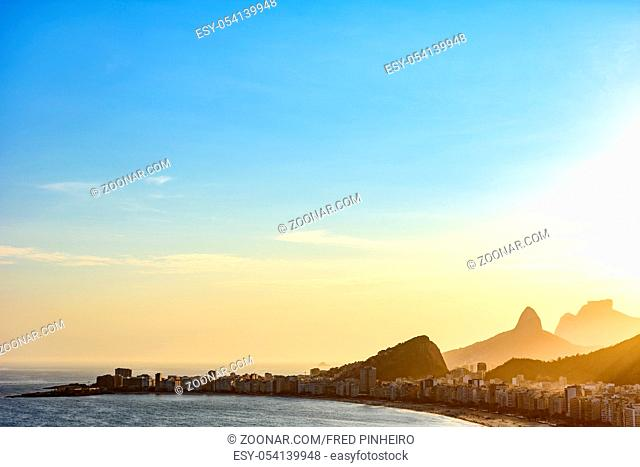 Copacabana beach in Rio de Janeiro during sunset with its buildings and the mountains in the background