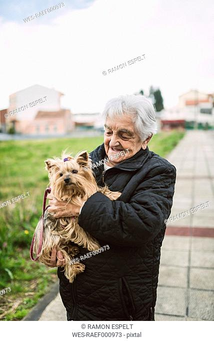 Happy senior woman with Yorkshire Terrier on her arms