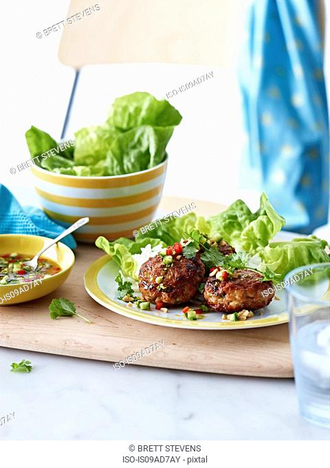 Plate of Thai prawn cakes with lettuce and dipping sauce
