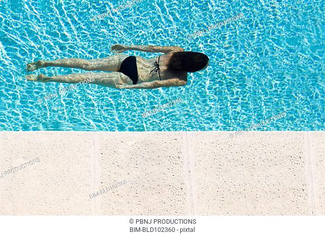 Mixed race woman swimming in pool