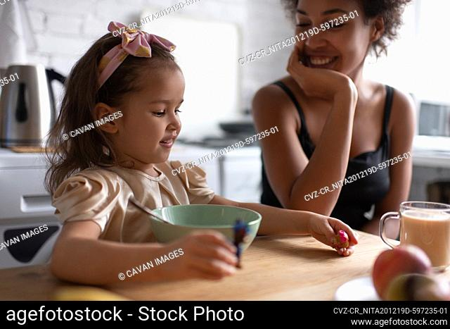 Cheerful ethnic girl playing during breakfast with mother